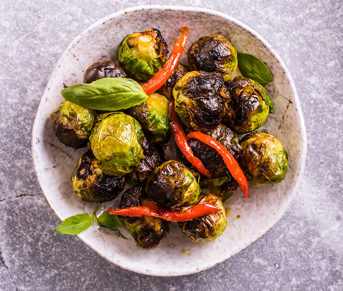 Roasted Brussels sprouts in plate on stone background. Top view. Closeup