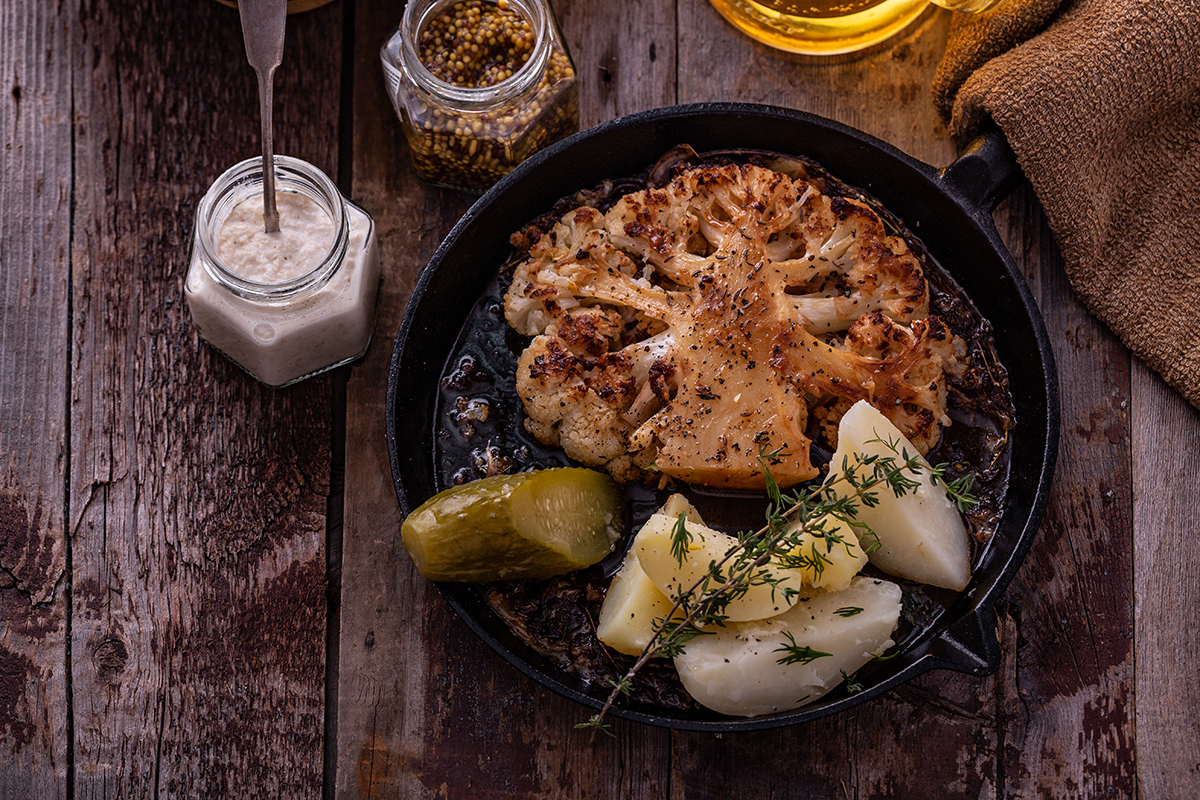 Vegetarian roasted cauliflower steak with potatoes on a frying pan.