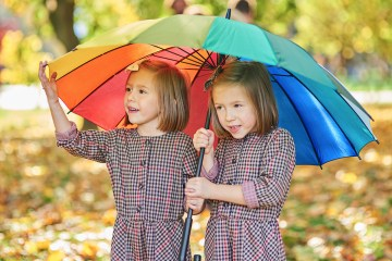 Twins looking for shelter with umbrella