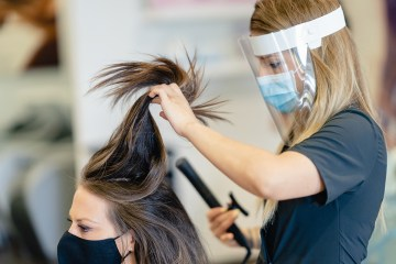 Hairdresser, protected by a mask, combing her client's hair with a hair iron in a salon.