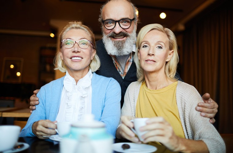 Senior bearded man embracing two blonde aged women during their hangout in cafe