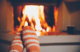 Feet in wool striped socks by the fireplace. Relaxing at Christm