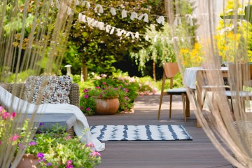 View of cozy garden with living room set on wooden deck