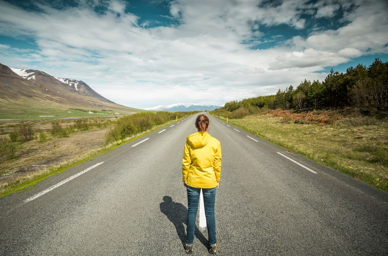 Beautiful woman contemplating a beautiful road surrounded by nature