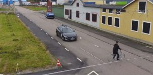 Image of a car approaching intersection with pretend houses behind it