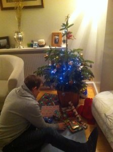 George putting presents under the Christmas tree