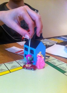 A big wooden house sitting on Monopoly's Piccadilly Circus, with Kinder toys posed in front