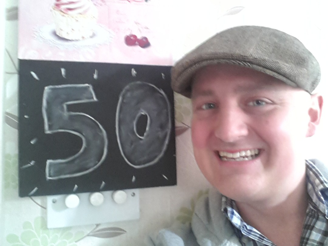 George by chalk-board with '50' written on it