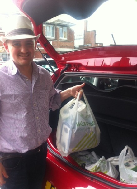 George putting shopping bags in the boot of the new car