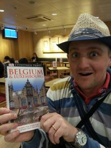 George at St Pancras station with a guide to Brussels