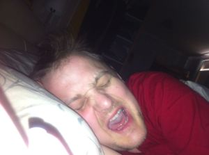 George in bed, pulling a face with his eyes shut