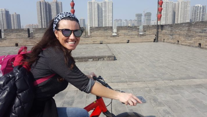 Mariacristina smiling and cycling, with the edge of Xi'an city wall in the background