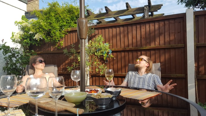 Rae and George looking happy sitting at a garden table with wine glasses and sunglasses