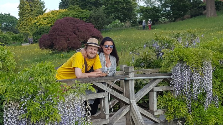 George and Mariacristina on a beautiful bridge with gorgeous plants either side at RHS Wisley