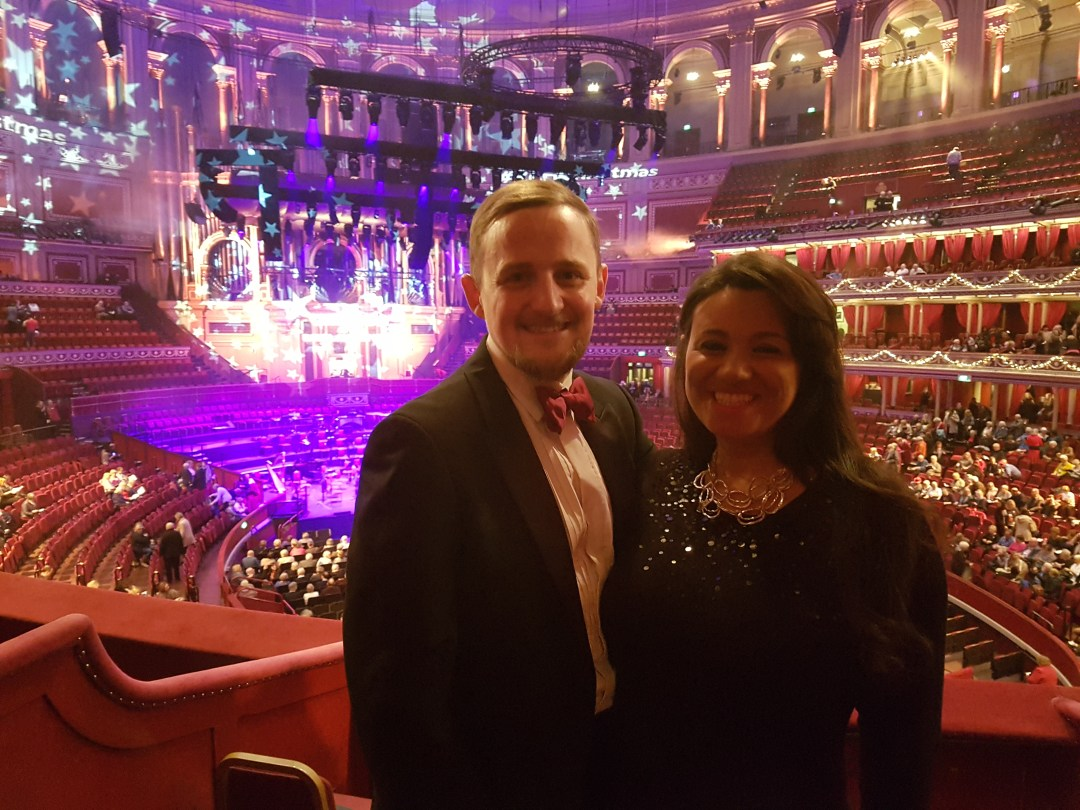 George and Mariacristina dressed up, in a box at the Royal Albert Hall, with the stage in the background