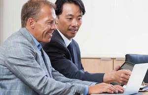 Two male colleagues wearing business suits working together on a computer
