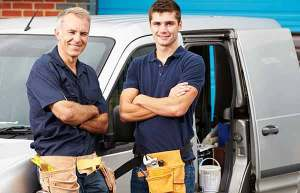 Owners of a Small Contracting Business Standing Next To a Van