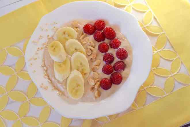 Peanut butter smoothie bowl topped with fresh raspberries, bananas, and chopped peanuts.