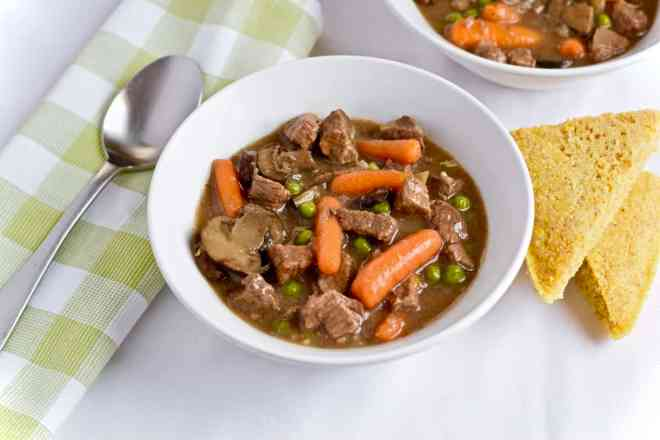 Beef stew with carrots in bowl with cornbread.