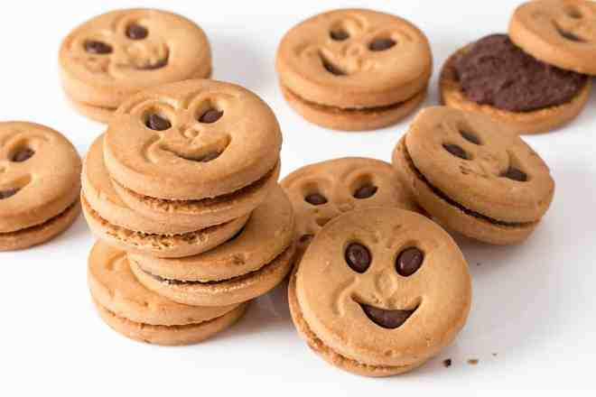 small chocolate cream cookies with smiling faces