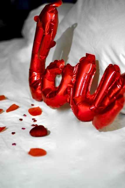 red plastic balloon on white textile