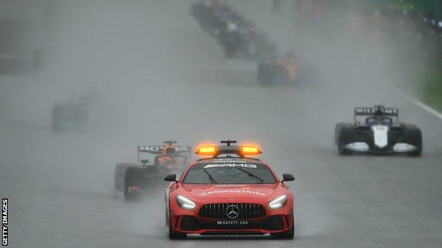 The safety car leads the drivers out around the track at Spa in the wet conditions