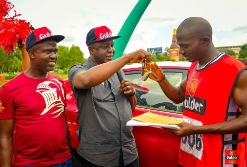 Emmanuel Agu, Marketing Manager, Gulder, More, 33, Life and Stout category; Ansel Alokha, Zonal Business Manager, East, both of Nigerian Breweries Plc. and Chinedu Odimgbe, winner of a brand new Hyundai Elantra car of 'The Chase' leg of the 2015 edition of the Gulder Ultimate Promo, during the prize presentation at Michael Okpara Square, Enugu