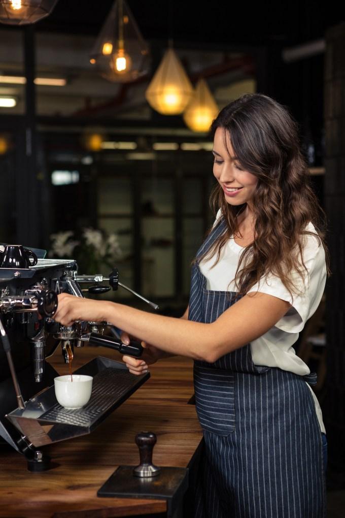 Barista preparing coffee with machine in coffee shop