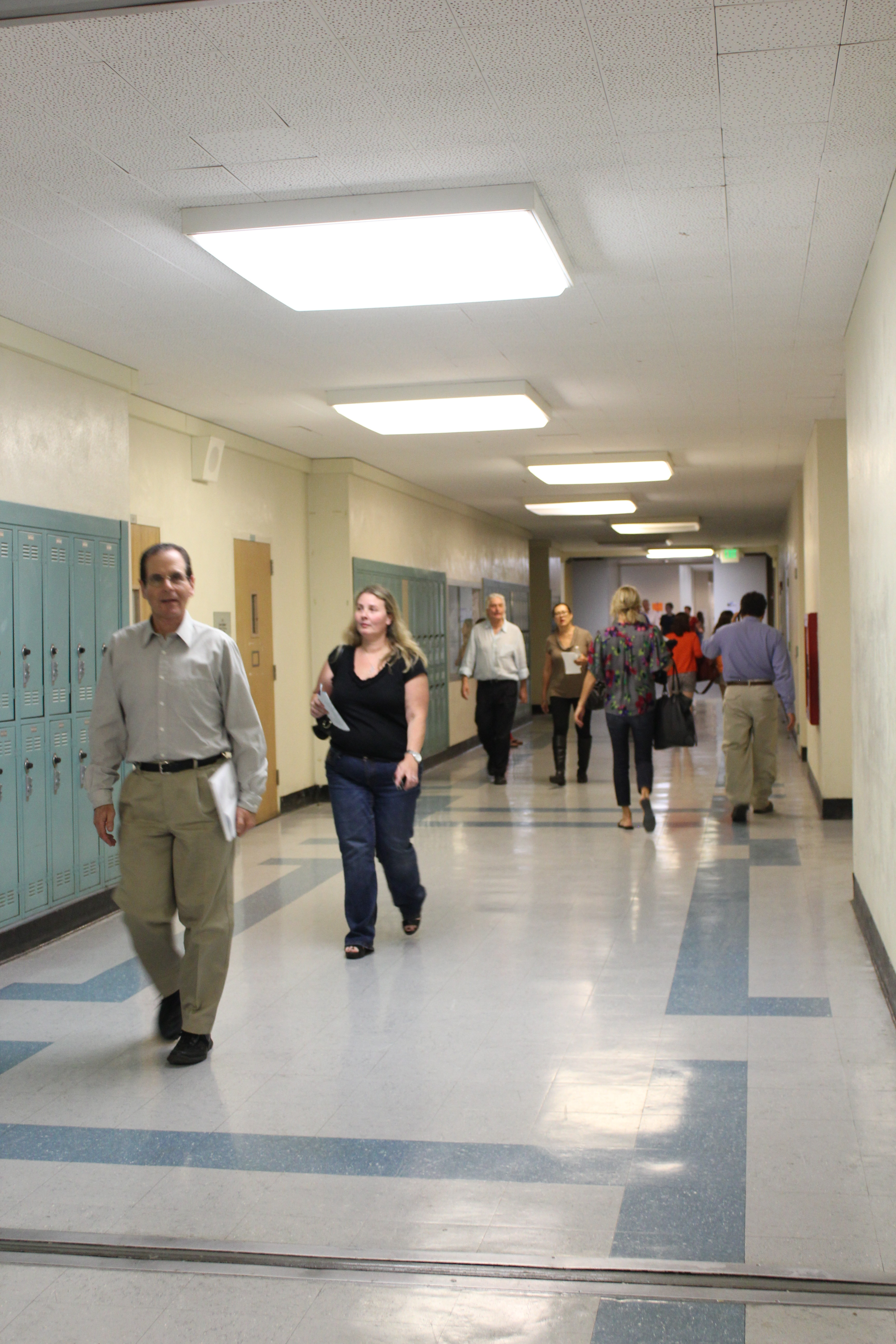 As the bell rings, parents look for their next class in the third floor hallway.