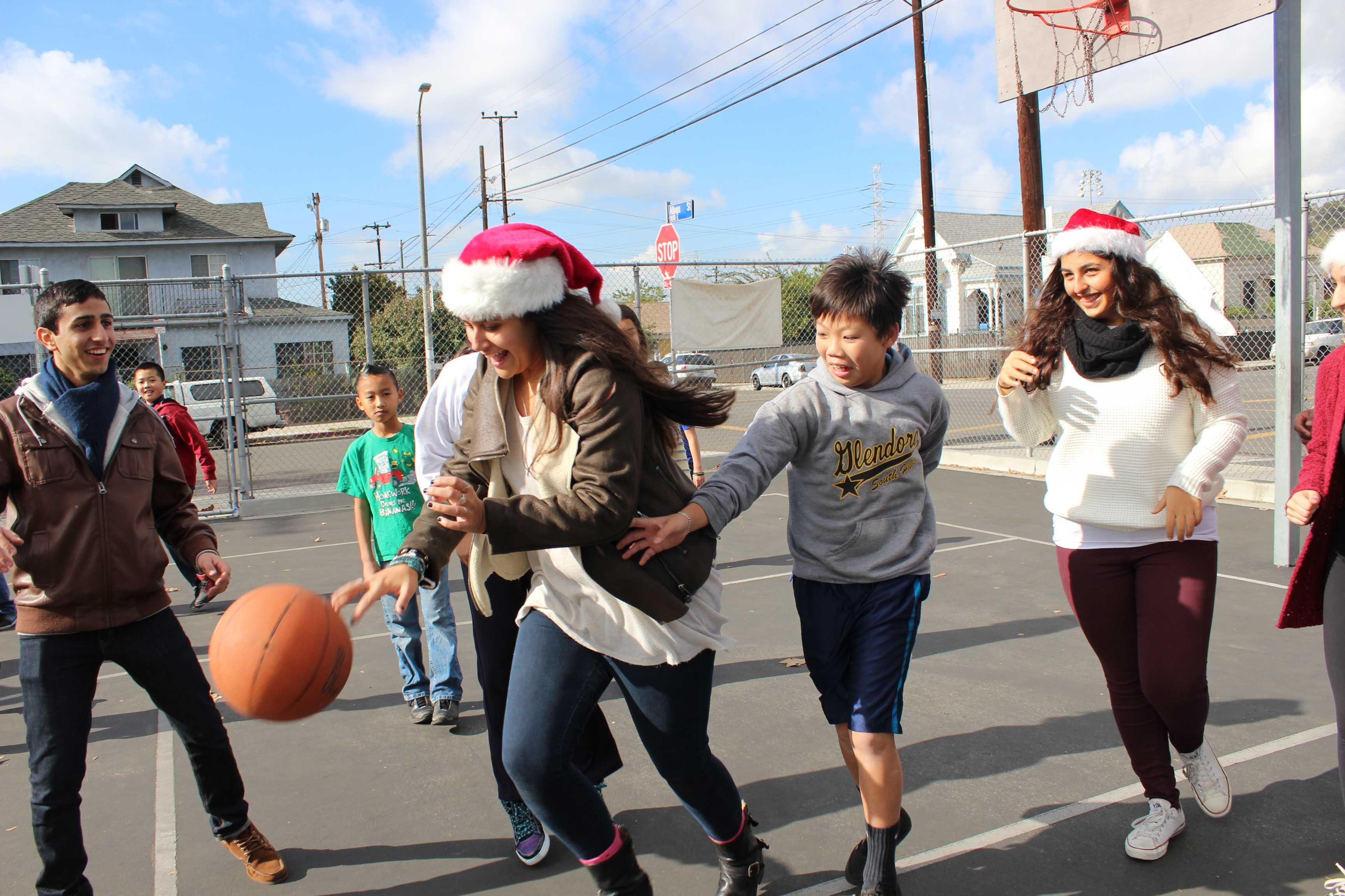 Seniors Alex Elgam, Matthew Ghermezi and Shana Kahrobaee play basketball with Albion students during recess.