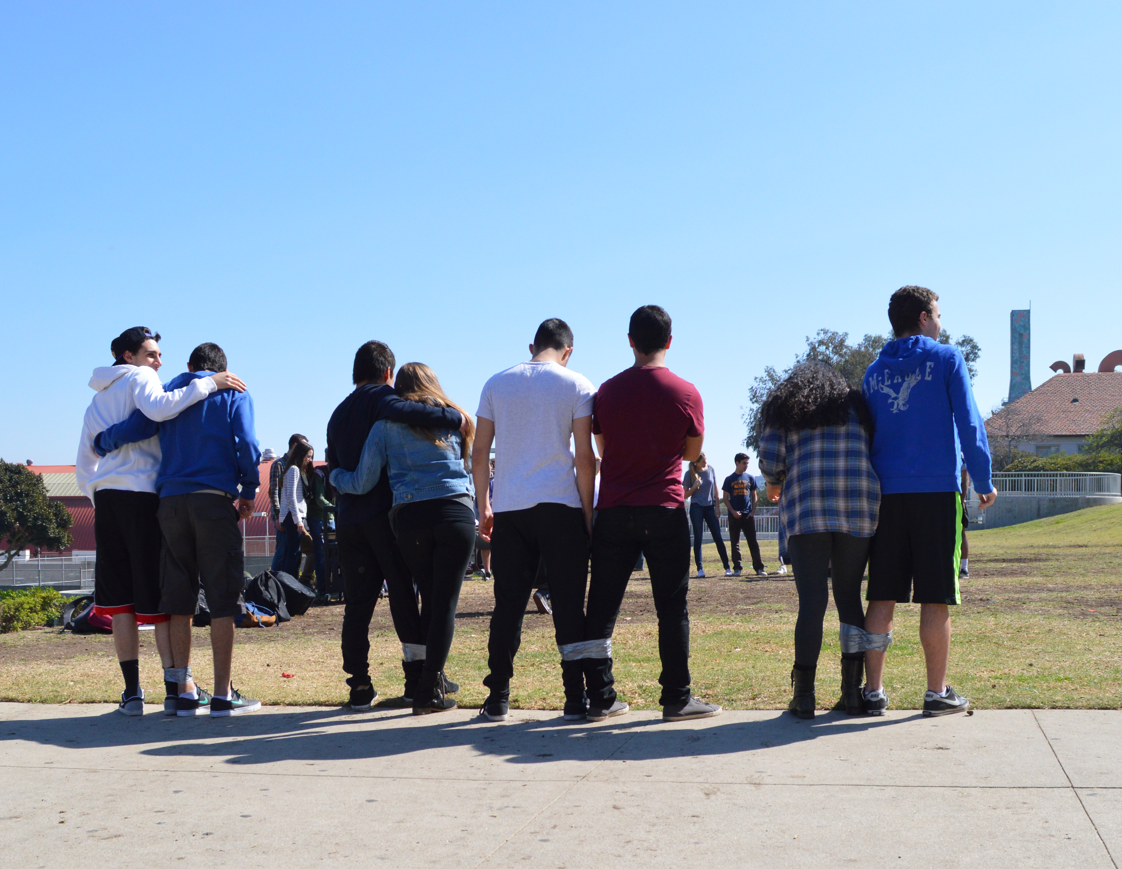 Pairs of juniors and seniors line up to take part in the final activity of the lunch period: the three-legged race.