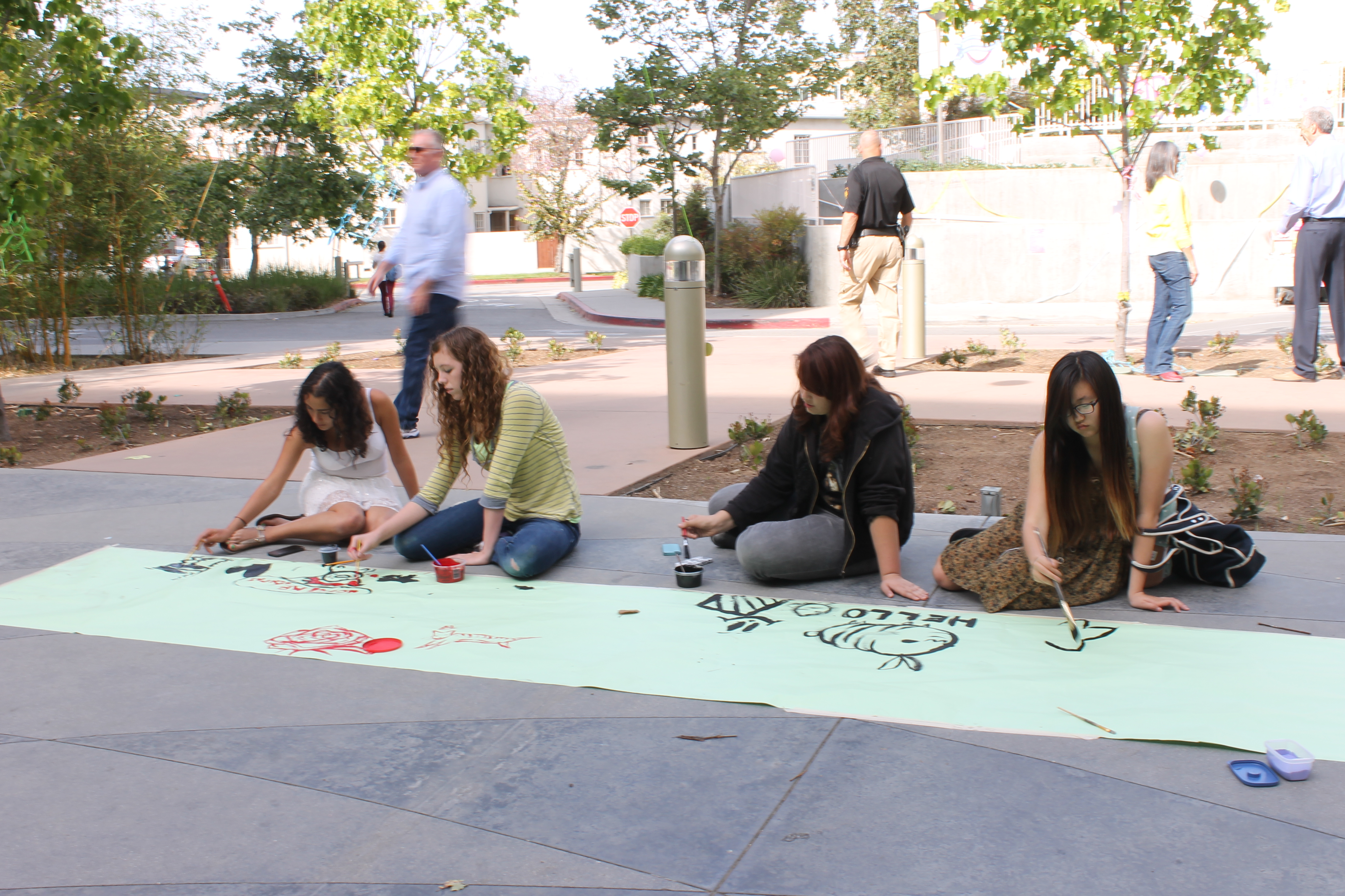 Participants paint on a long spread of paper at the painting station.