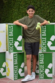 Sophomore Jason Mandel poses in front of Recycleballs' equipment.