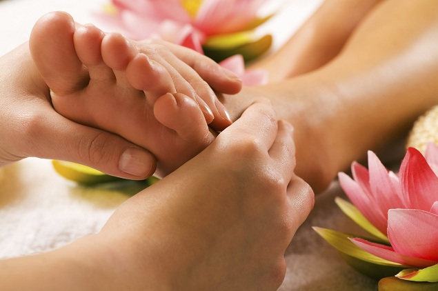 Reflexology on the foot with pink flowers