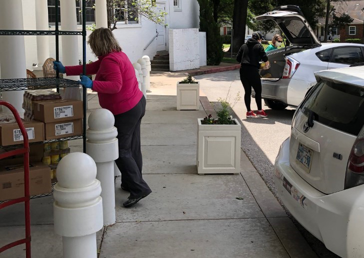 Volunteers loading cars with food