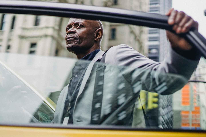 serious black businessman opening taxi door