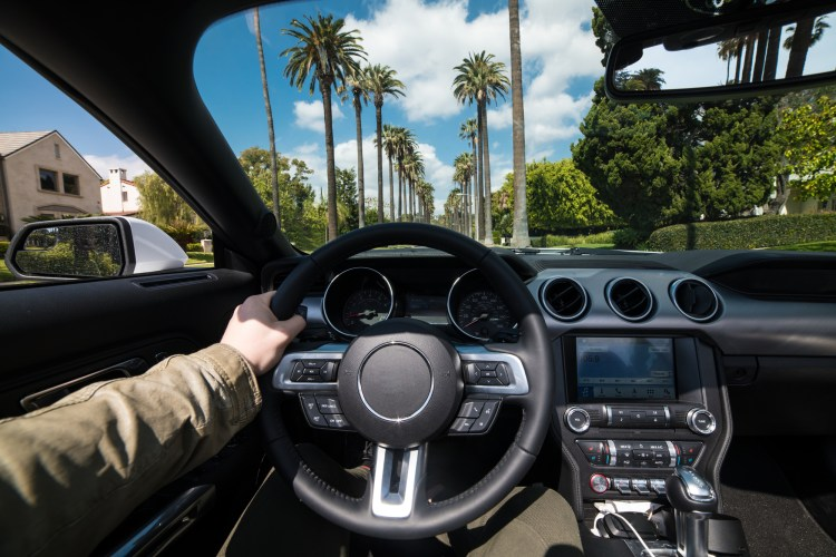 Man driving luxury car in Beverly Hills, California at hot summer day. Luxury lifestyle concept.