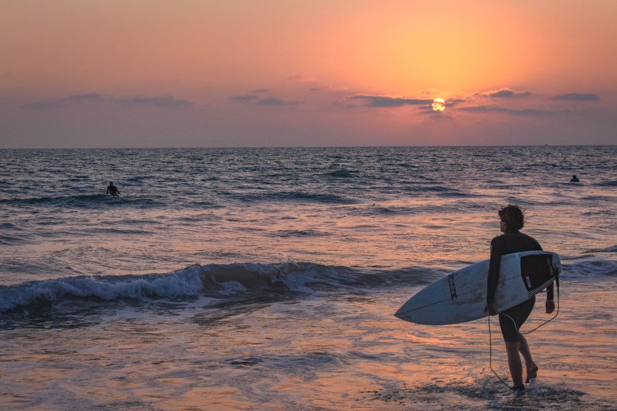 San Clemente surfer heading into the water at sunset