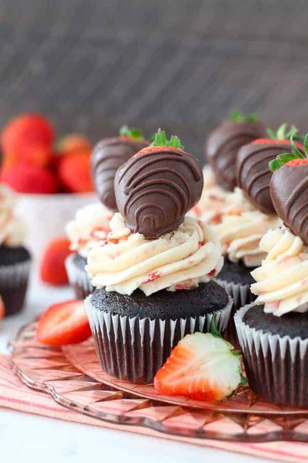 A close up of a chocolate covered strawberry cupcake on a pink glass cake plate.