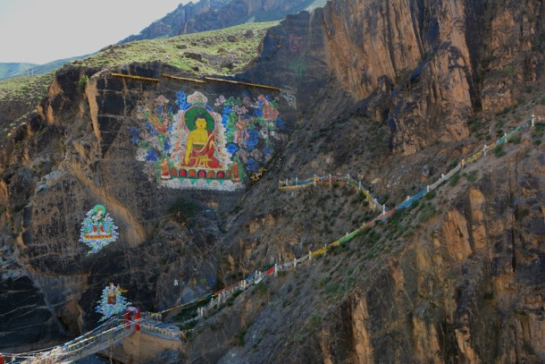 Tibetan Tangka paintings on the mountain rocks.
