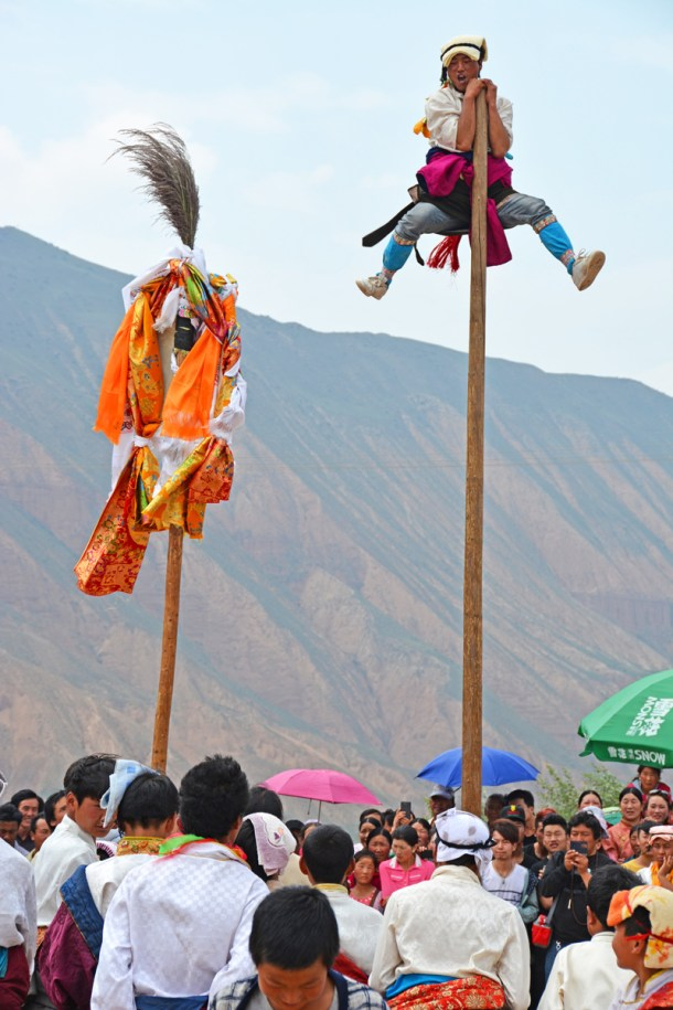 A Tibetan young man from the outer players reaches the top of a pole, known as the water deities' tree (Klu-sdong).