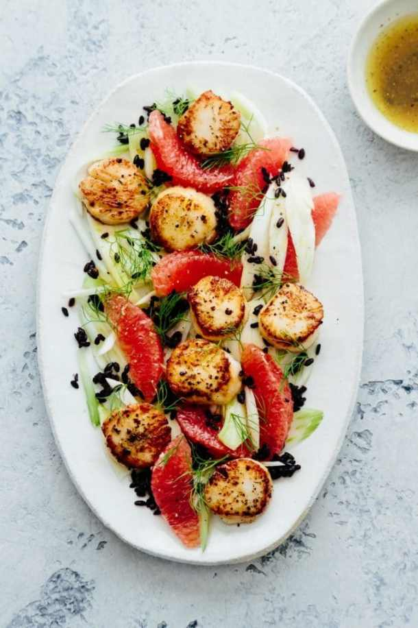 a platter of seared scallops, grapefruit, fennel, and wild rice salad next to a bowl of salad dressing