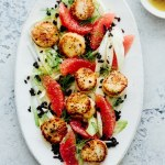 a platter of scallops, grapefruit, fennel, and wild rice salad next to a bowl of salad dressing