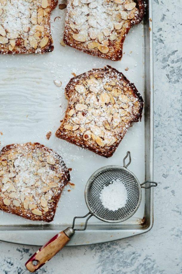 Four slices of Meyer lemon bostocks and sieve on baking sheet and