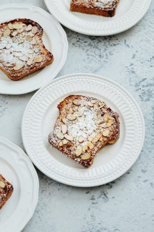 four white plates with slices of Meyer lemon bostocks