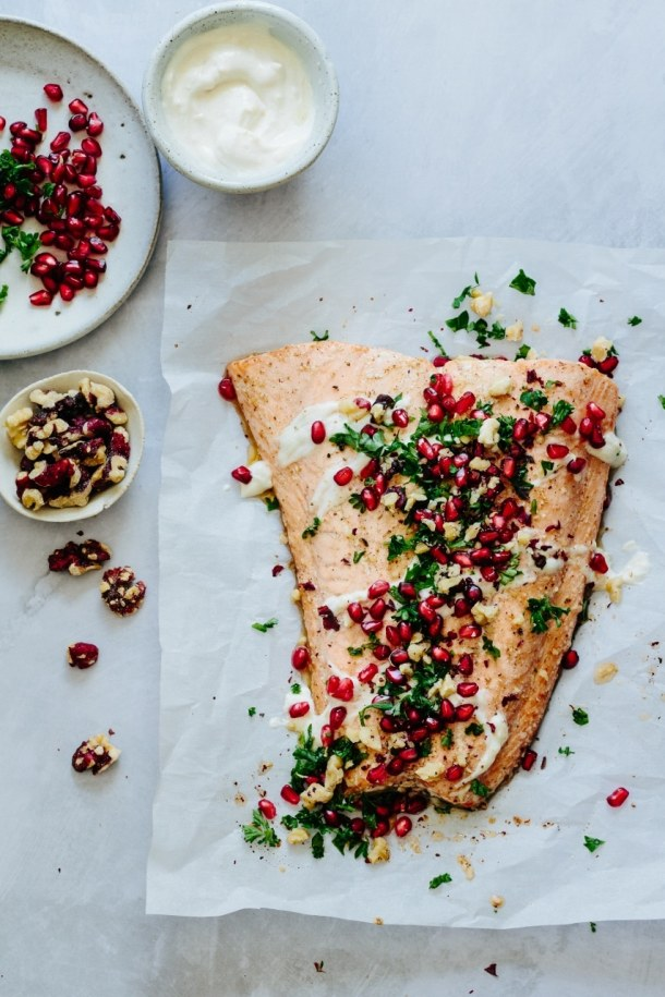 salmon with plate of pomegranate seeds and parsley, bowl of tahini dressing, and bowl of walnuts