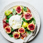 a plate of salad with figs, burrata, prosciutto, and basil