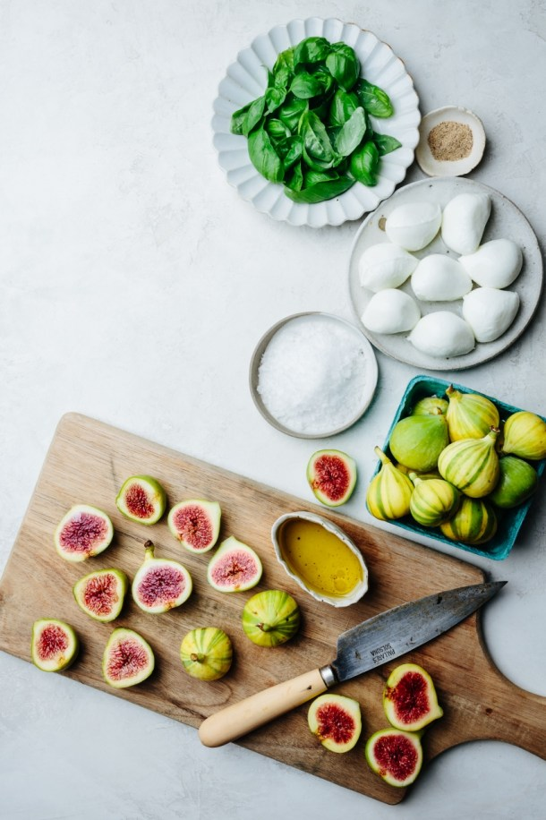 cutting board with knife and fresh figs, a basket of figs, plate of mozzarella, plate of basil, plate of salt, and bowl of olive oil