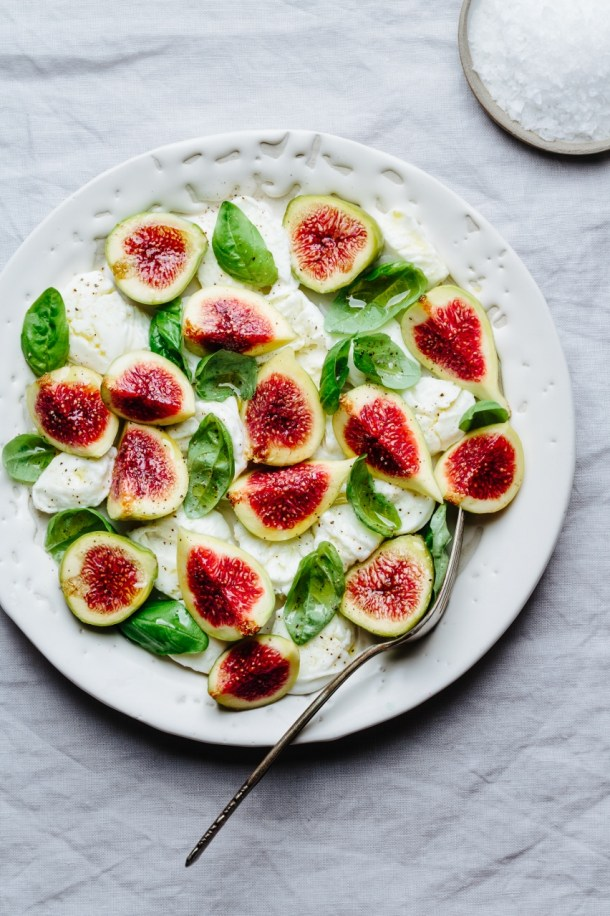 a plate of fig caprese salad with fresh figs, mozzarella, and basil leaves and a plate of salt