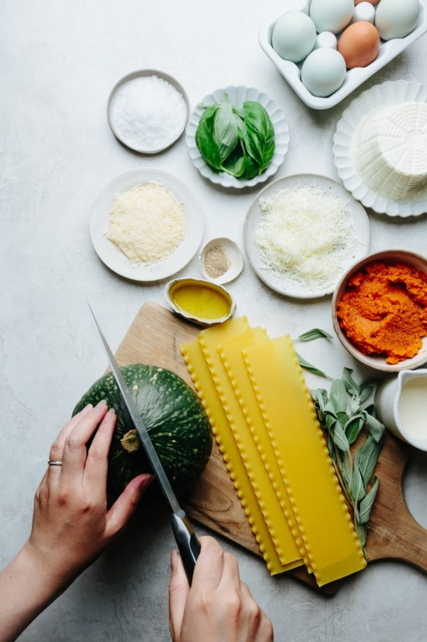 photo of ingredients for lasagna, left hand holding a pumpkin and right hand holding a knife to cut the kabocha squash, lasagna sheets, sage, basil, pumpkin, cheeses, eggs, and heavy cream